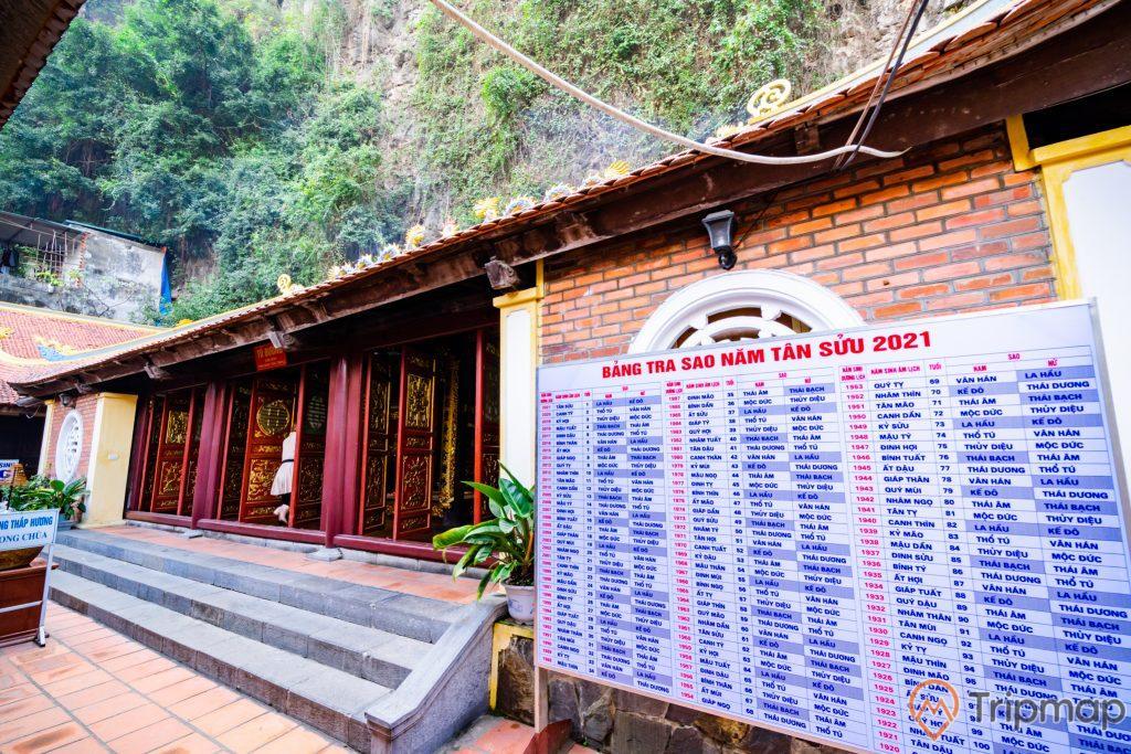 Chùa Long Tiên, bảng tra sao, nền gạch màu đỏ, bậc thang màu xám, cửa gỗ có hoa văn màu vàng, núi đá phía sau, ảnh chụp ban ngày