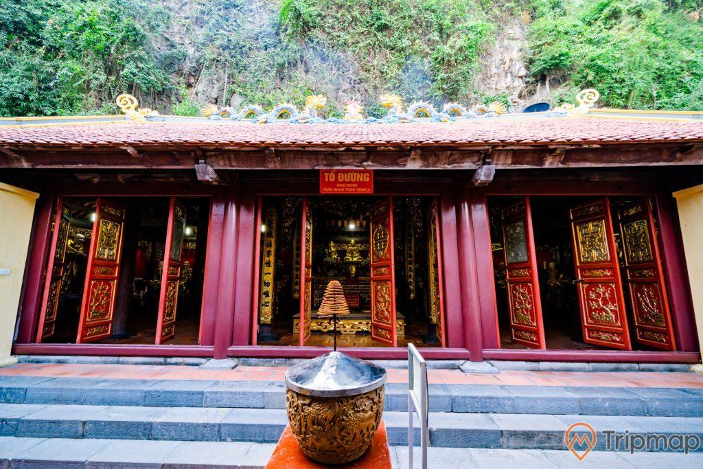 Chùa Long Tiên, Tổ Đường, lư hương, cánh cửa màu đỏ có hoa văn, bậc thang bằng đá màu xám, mái ngói màu đỏ, tượng rồng bằng đá, ngọn núi đá phía sau, ảnh chụp ban ngày