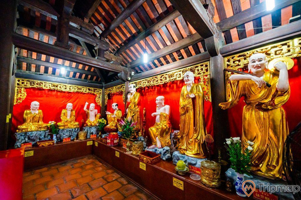Chùa Long Tiên, nhiều tượng thờ màu vàng, nền gạch màu đỏ, lư hương, lọ hoa, tấm rèm màu đỏ, trần nhà bằng gỗ màu nâu