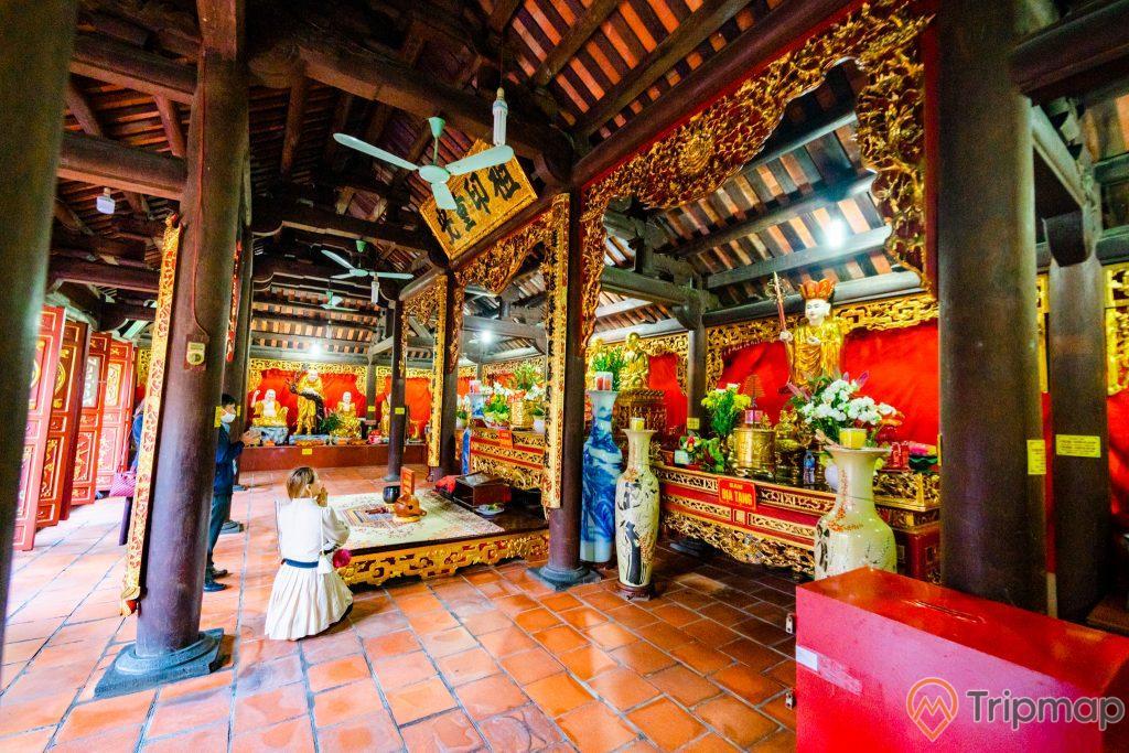 Chùa Long Tiên, Tổ Đường, nền gạch màu đỏ, người đang cầu nguyện, lọ hoa, nhiều cột nhà màu nâu, cây quạt trần, trần nhà bằng gỗ màu nâu