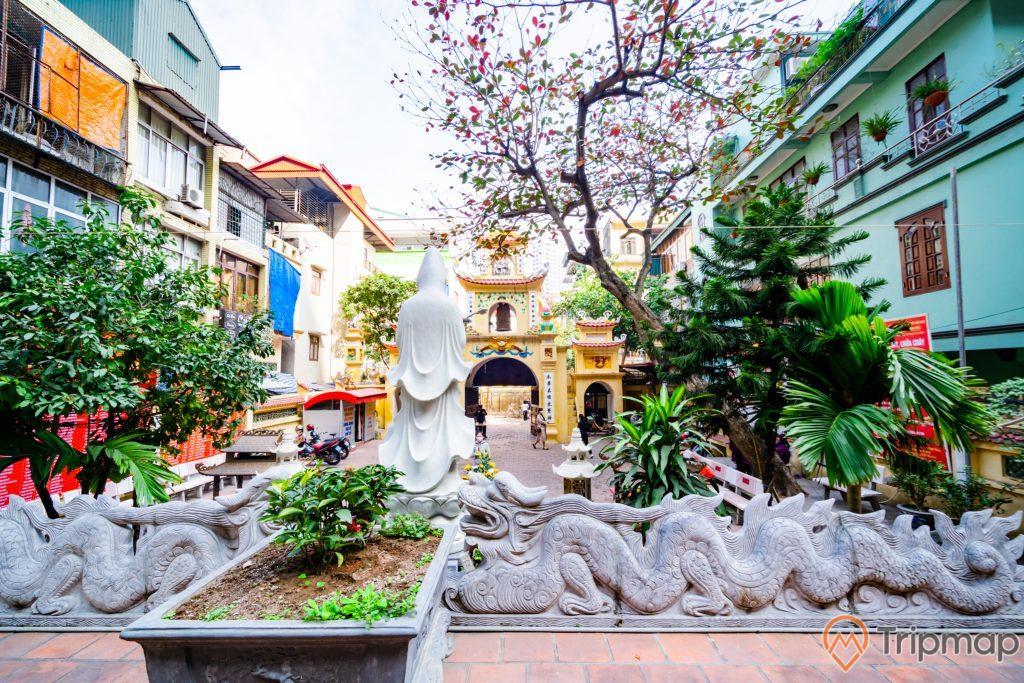 Chùa Long Tiên, tượng Quan Thế Âm Bồ Tát, tượng rồng bằng đá màu xám, chậu cây, nhiều cây xanh, nhà dân sơn màu xanh, cổng chùa sơn màu vàng, ảnh chụp ban ngày