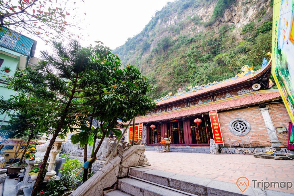 Chùa Long Tiên, nền gạch màu đỏ, nhiều cây xanh, bậc thang màu xám bằng đá, ngọn núi đá to nhiều cây xanh, lư hương, ảnh chụp ban ngày