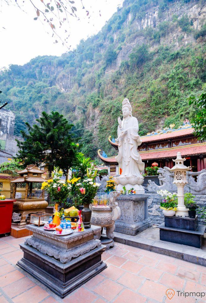 Chùa Long Tiên, tượng Phật Quan Thế Âm Bồ Tát, Lư Hương, nền gạch màu đỏ, nhiều cây xanh, ngọn núi đá nhiều cây xanh phía sau, ảnh chụp ban ngày