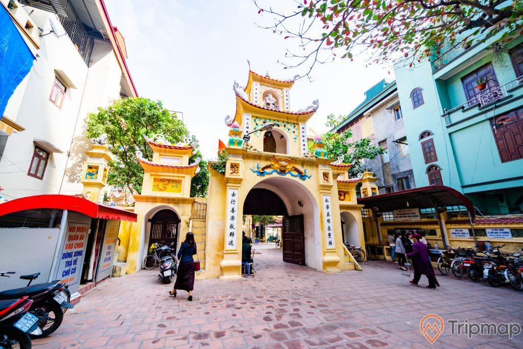Chùa Long Tiên, cổng Tam Quan Nội, nền gạch màu đỏ, cổng sơn màu vàng, nhiều xe mày, nhà dân sơn màu xanh, ảnh chụp ban ngày