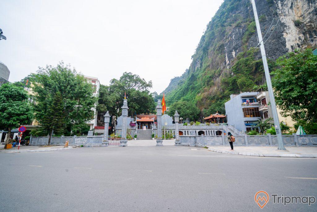 Đền thờ Đức Ông Trần Quốc Nghiễn, nền đường màu xám, cây cột đèn, lá cờ Việt Nam, nhiều cây xanh, ngọn núi đá có cây xanh, ảnh chụp ban ngày