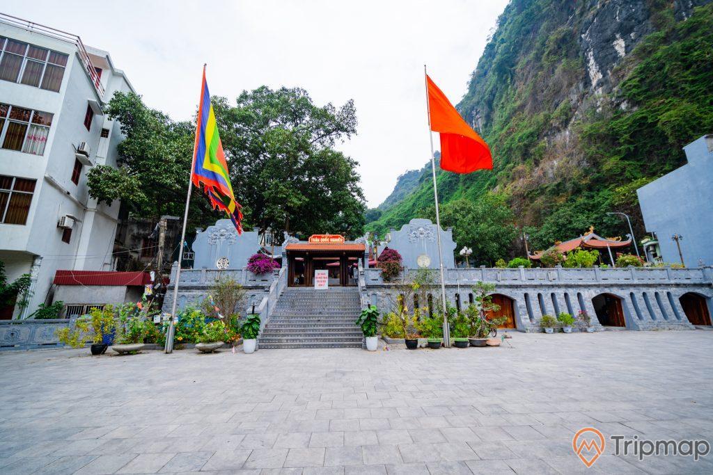 Đền thờ Đức Ông Trần Quốc Nghiễn, lá cờ Việt Nam, nền đường bằng gạch màu xám, bậc thang màu xám, nhiều chậu cây, ngọn núi đá có cây xanh, ảnh chụp ban ngày