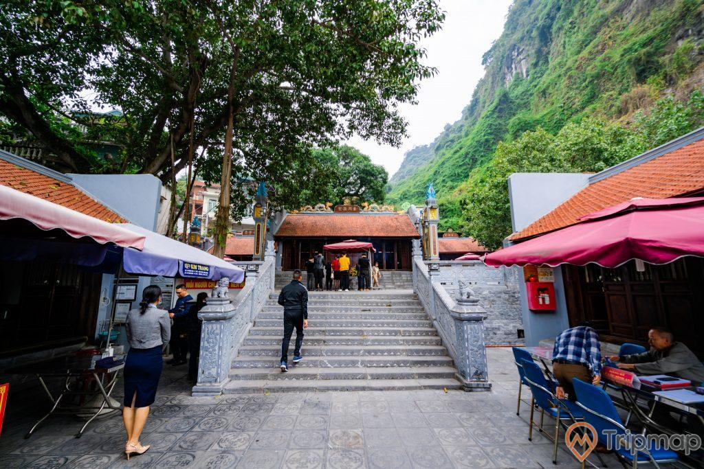 Đền thờ Đức Ông Trần Quốc Nghiễn, nhiều người đang đi trên nền gạch màu xám, bậc thang màu xám, nhiều ghế màu xanh, mái ngói màu đỏ, nhiều cây xanh, đền thờ phía xa, ngọn núi đá màu xám có cây xanh, ảnh chụp ban ngày