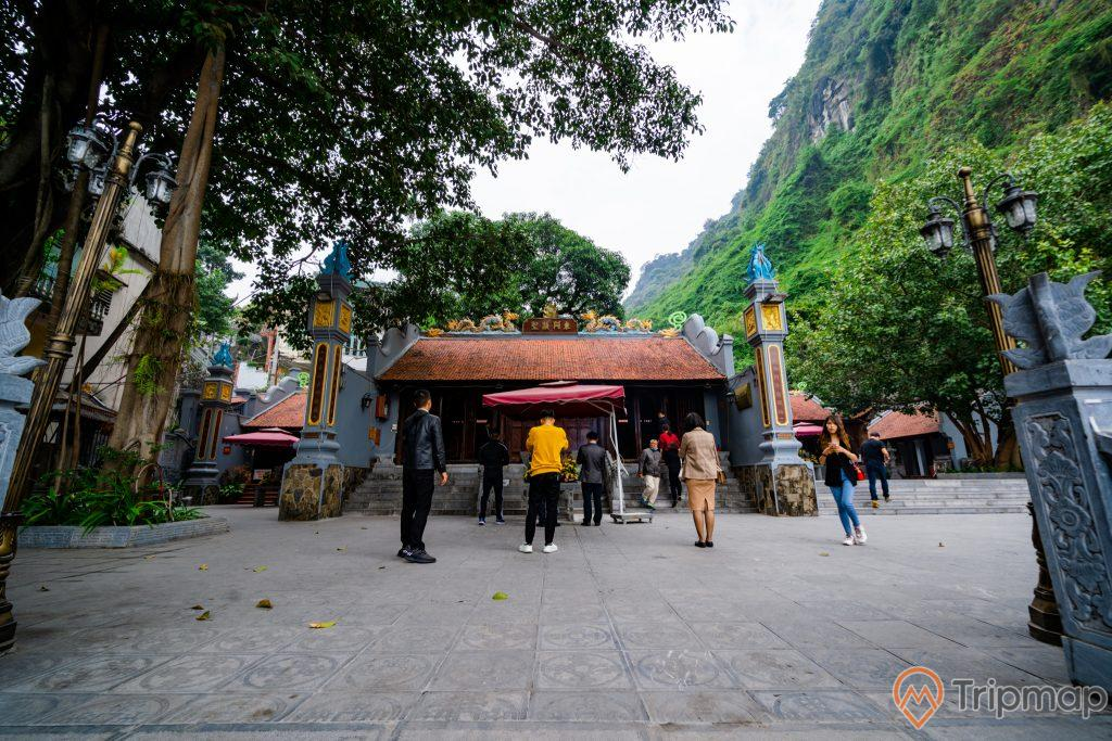Đền thờ Đức Ông Trần Quốc Nghiễn, nền gạch màu xám, nhiều người đang đứng trên nền gạch, nhiều cây xanh, mái ngói đỏ, ngọn núi đá có cây xanh, ảnh chụp ban ngày