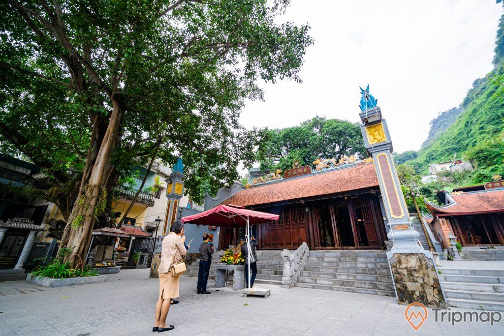Đền thờ Đức Ông Trần Quốc Nghiễn, bậc thang màu xám, nhiều người đang đứng trên nền gạch màu xám, mái ngói màu đỏ, cây xanh, trời sáng, ảnh chụp ban ngày