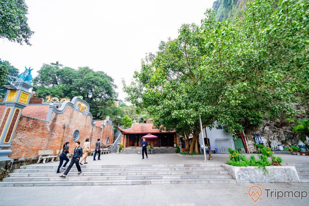 Đền thờ Đức Ông Trần Quốc Nghiễn, bậc thang màu xám, nhiều người đang đi trên nền gạch màu xám, nhiều cây xanh, bức tường gạch màu đỏ, ảnh chụp ban ngày