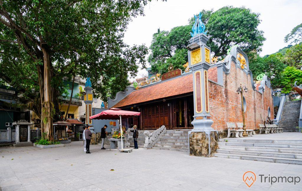 Đền thờ Đức Ông Trần Quốc Nghiễn, nền đường màu xám, bậc thang màu xám, đền thờ bằng gạch màu đỏ, nhiều cây xanh, ảnh chụp ban ngày