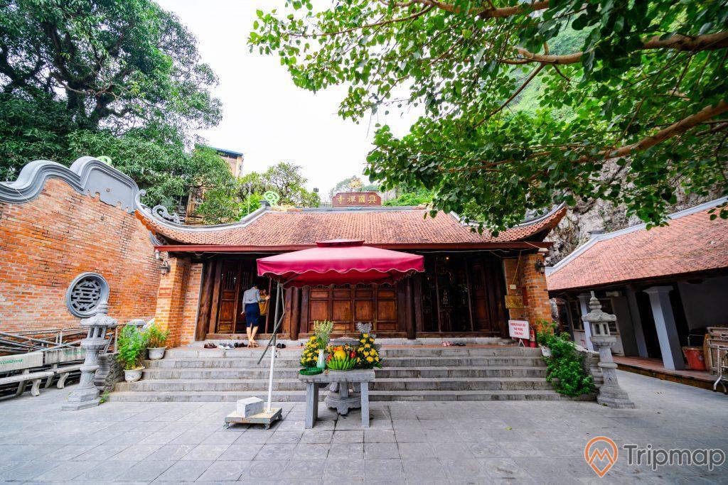 Đền thờ Đức Ông Trần Quốc Nghiễn, nền đường màu xám, bậc thang màu xám, mái ngói màu đỏ, bức tường bằng gạch màu đỏ, nhiều cây xanh, ảnh chụp ban ngày