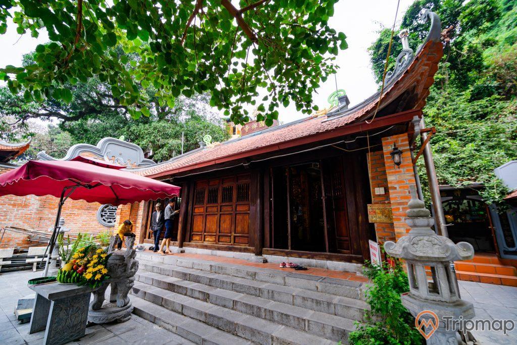 Đền thờ Đức Ông Trần Quốc Nghiễn, bậc thang màu xám, cánh cửa bằng gỗ màu nâu, nhiều cây xanh, ảnh chụp ban ngày