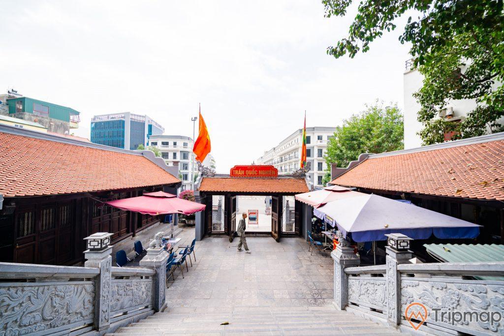 Đền thờ Đức Ông Trần Quốc Nghiễn, nền đường màu xám, cầu thang bằng đá màu xám, nhiều mái ngói màu đỏ, cờ Việt Nam, nhà cao tầng ở phía xa, ảnh chụp ban ngày