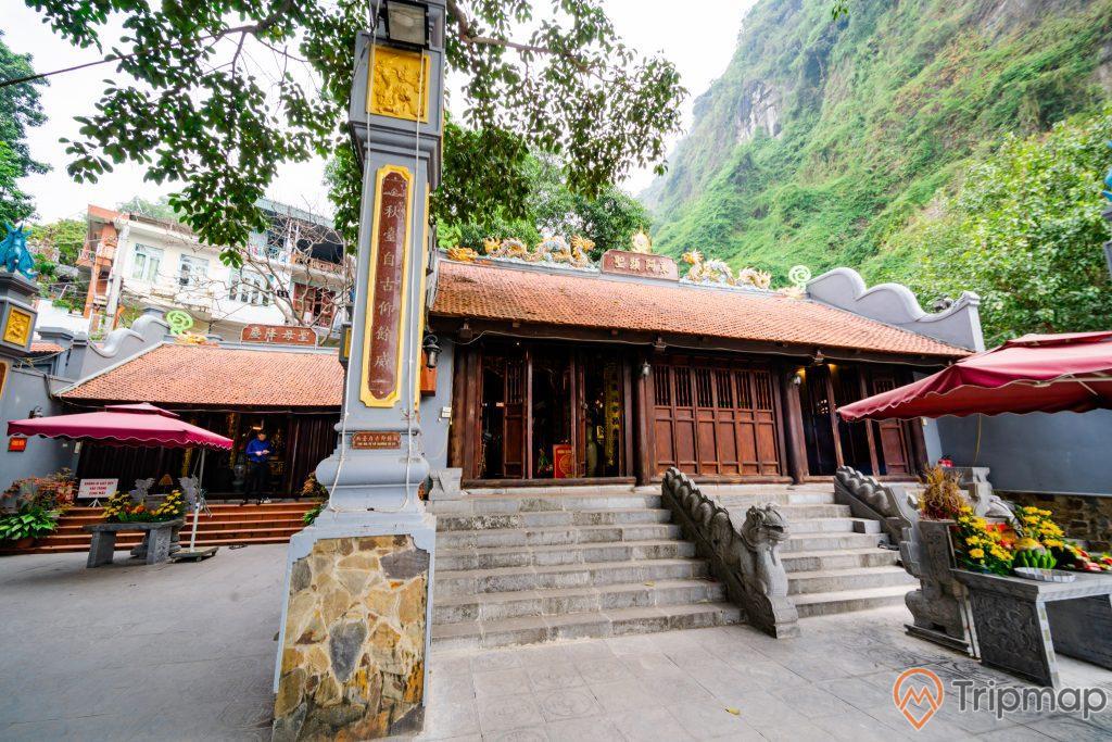 Đền thờ Đức Ông Trần Quốc Nghiễn, nền gạch màu xám, bậc thang bằng đá màu xám, mái ngói màu đỏ, nhiều cánh cửa bằng gỗ màu nâu, ngọn núi nhiều cây xanh bên cạnh, ảnh chụp ban ngày