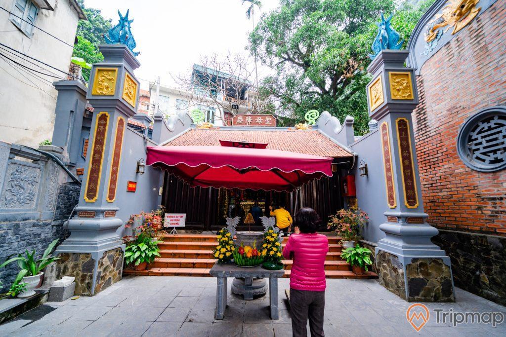 Đền thờ Đức Ông Trần Quốc Nghiễn, người mặc áo đỏ đang cầu nguyện, nền đường bằng gạch màu xám, bậc thang màu đỏ, nhiều chậu cây, lư hương, mái ngói màu đỏ, bức tường bằng gạch màu đỏ, ảnh chụp ban ngày