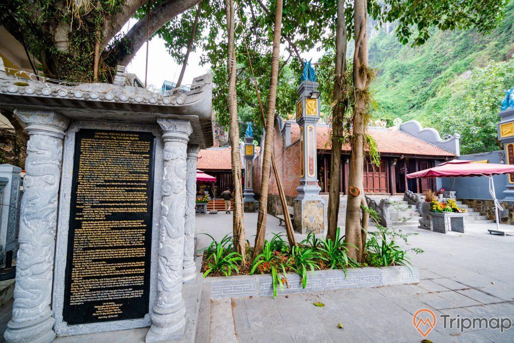Đền thờ Đức Ông Trần Quốc Nghiễn, bia đá, ảnh chụp ban ngày, nhiều cây xanh, mái ngoái màu đỏ, ngọn núi đá có cây xanh bên cạnh