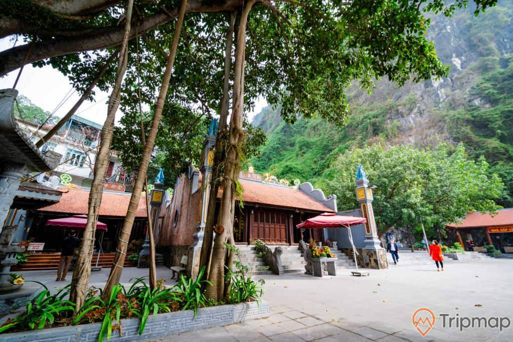 Đền thờ Đức Ông Trần Quốc Nghiễn, nhiều cây xanh, nền đường màu xám, bậc thang màu xám, mái ngói màu đỏ, ngọn núi đá có cây xanh, ảnh chụp ban ngày