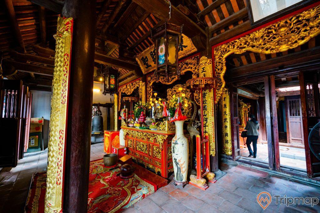 Đền thờ Đức Ông Trần Quốc Nghiễn, nền gạch màu đỏ, cây cột nhà màu nâu, gian thờ màu vàng, trần nhà bằng gỗ màu nâu