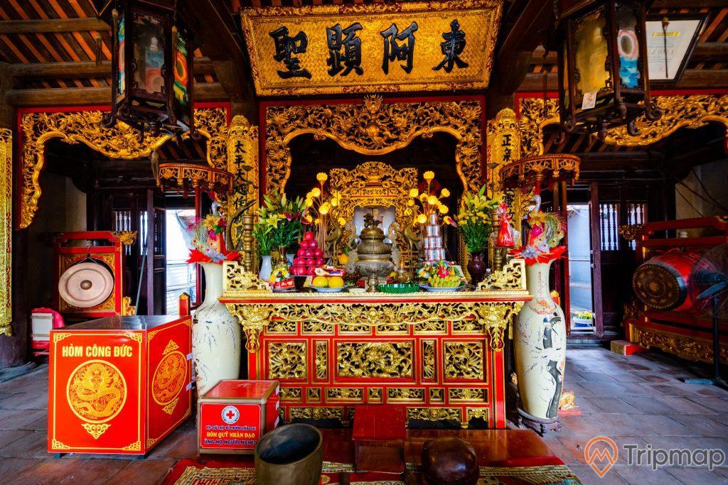 Đền thờ Đức Ông Trần Quốc Nghiễn, gian thờ màu có hoa văn màu vàng, hòm công đức, 2 cái bình màu trắng, nền gạch màu đỏ, trần nhà bằng gỗ màu nâu