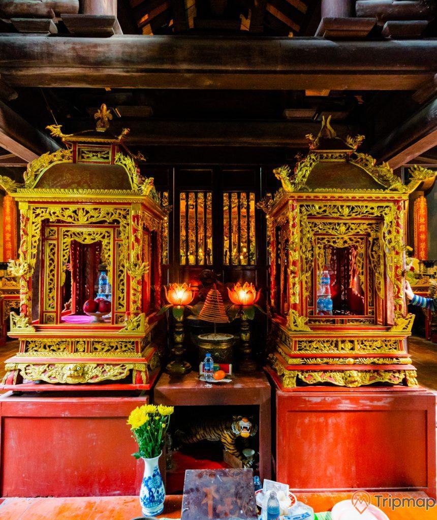 Đền thờ Đức Ông Trần Quốc Nghiễn, 2 gian thờ có hoa văn màu vàng, lọ hoa, trần nhà bằng gỗ màu nâu, đèn hình hoa sen