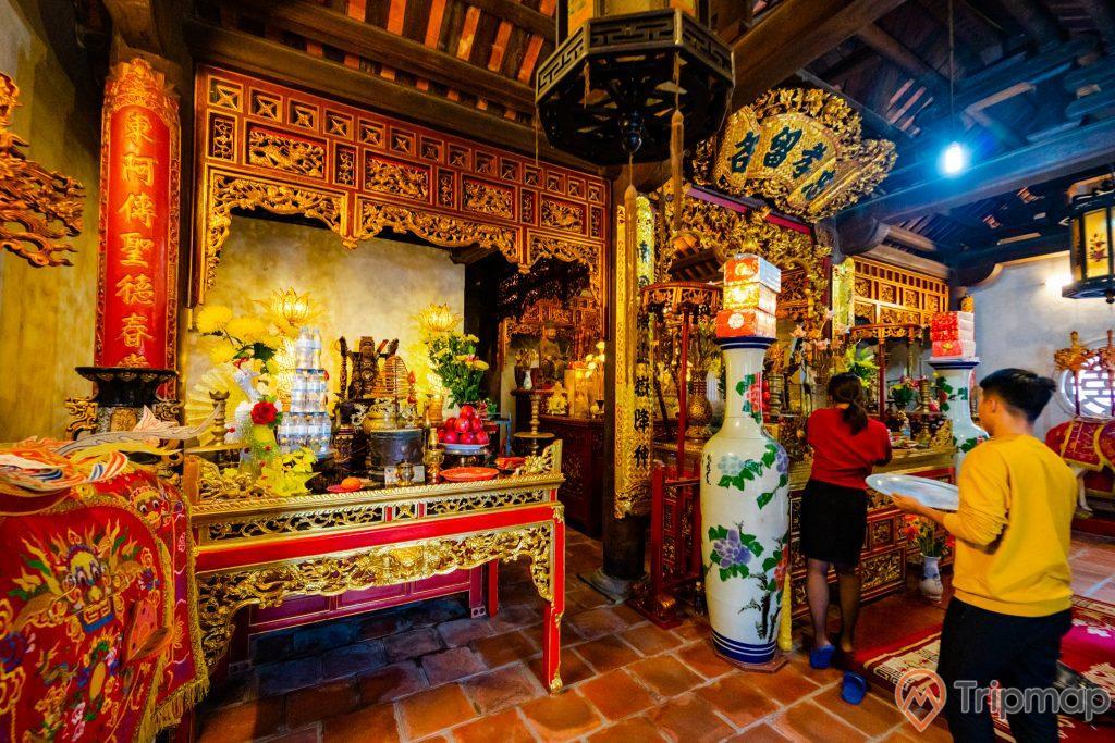 Đền thờ Đức Ông Trần Quốc Nghiễn, nền gạch màu đỏ, gian thờ màu vàng nhiều hoa văn, người mặc áo vàng đang bê đồ, nền nhà bằng gỗ màu nâu