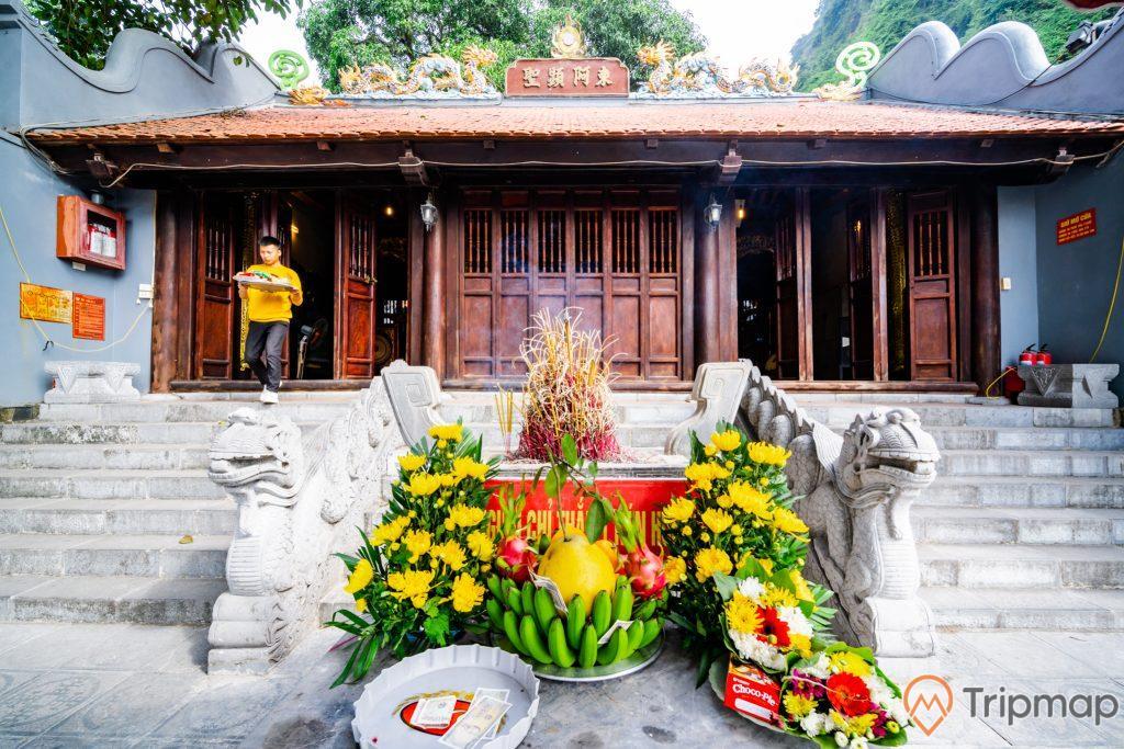Đền thờ Đức Ông Trần Quốc Nghiễn, nải chuối xanh, nhiều hoa màu vàng, lư hương, nền gạch màu xám, bậc thang màu xám bằng đá, nhiều cánh cửa màu nâu, mái ngói màu đỏ, ảnh chụp ban ngày