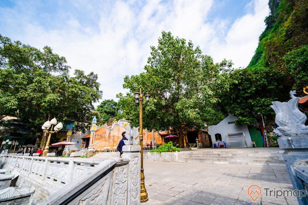 Đền thờ Đức Ông Trần Quốc Nghiễn, nền đường màu xám, cây đèn màu vàng, nhiều cây xanh, trời nắng, trời xanh nhiều mây, ảnh chụp ban ngày