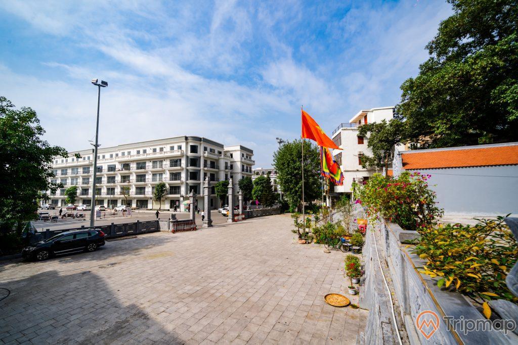 Đền thờ Đức Ông Trần Quốc Nghiễn, nền đường bằng gạch màu xám. lá cờ việt nam, xe ô tô màu đen, nhiều cây xanh, tòa nhà cao tầng phía xa, trời xanh nhiều mây, trời nắng, ảnh chụp ban ngày