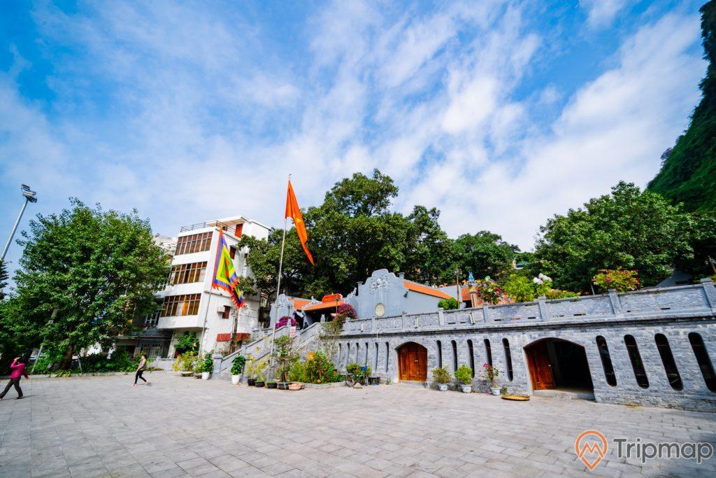 Đền thờ Đức Ông Trần Quốc Nghiễn, nền đường bằng gạch màu xám, nhiều cây xanh, lá cờ việt nam, trời xanh nhiều mây, ảnh chụp ban ngày