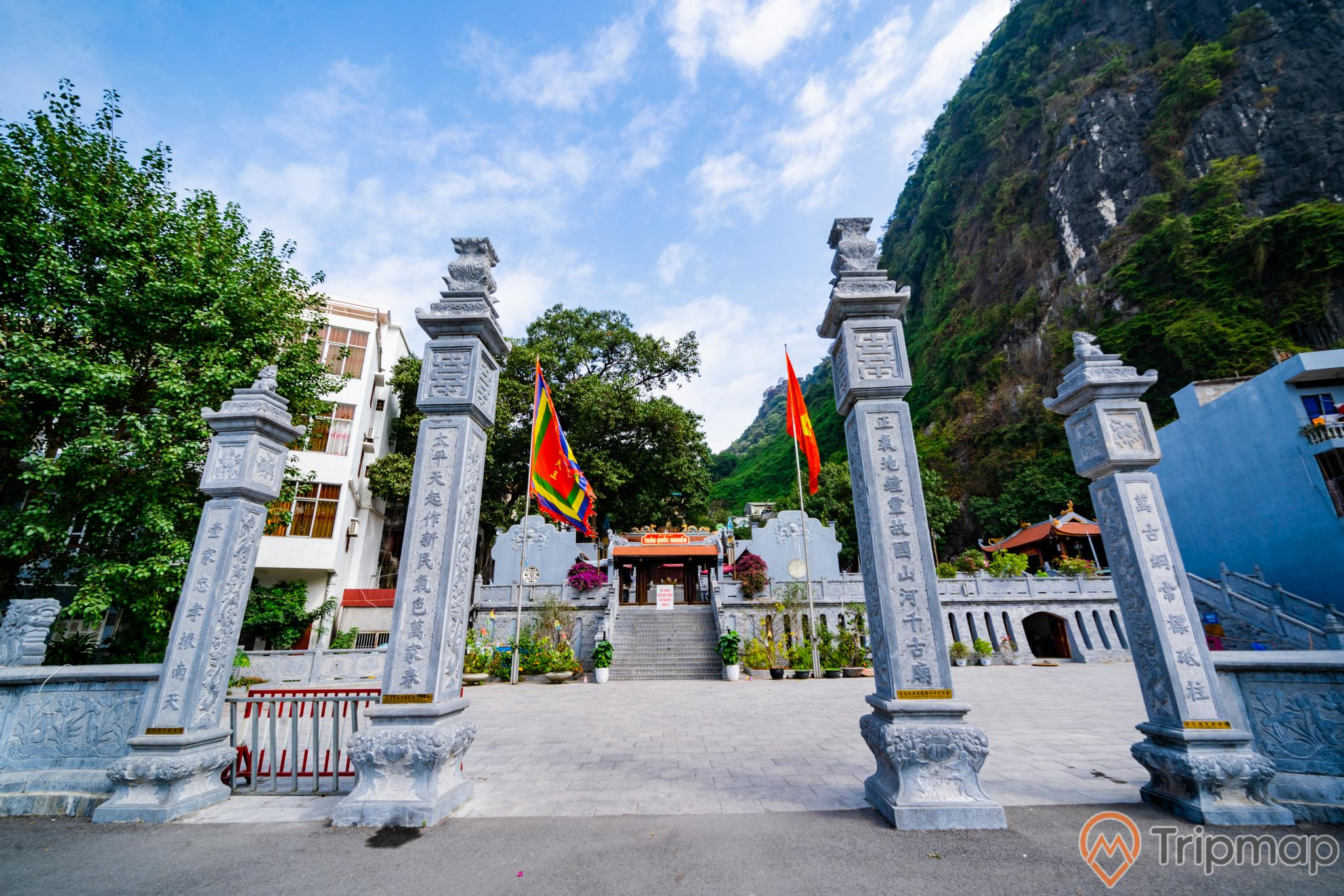 Đền thờ Đức Ông Trần Quốc Nghiễn, nhiều cây cột đá có chữ hán, nền đường màu xám, lá cờ việt nam, nhiều cây xanh, ngọn núi đá to có cây xanh bên cạnh, trời xanh nhiều mây, ảnh chụp ban ngày