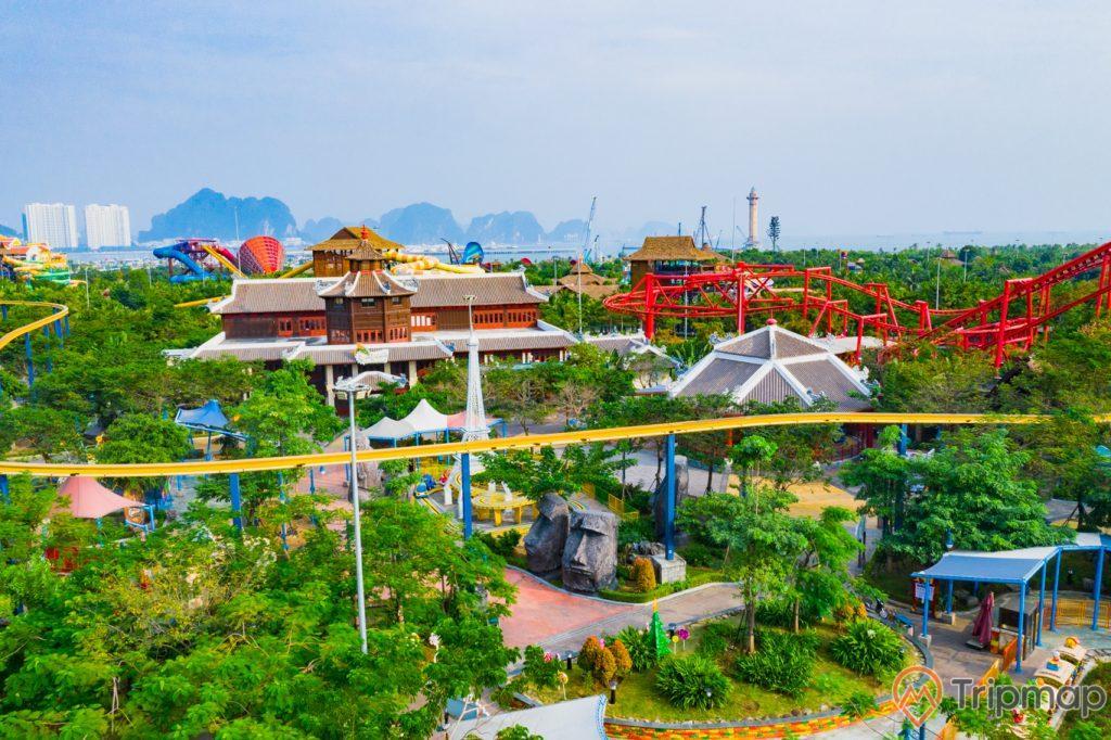 Khu vui chơi giải trí Sun World Ha Long Complex, nhiều cây xanh, tòa nhà có mái ngoái màu nâu, tảng đá hình mặt người, nhiều ngọn núi đá có cây xanh phía xa, trời xanh nhiều mây, ảnh chụp ban ngày, ảnh chụp từ trên cao