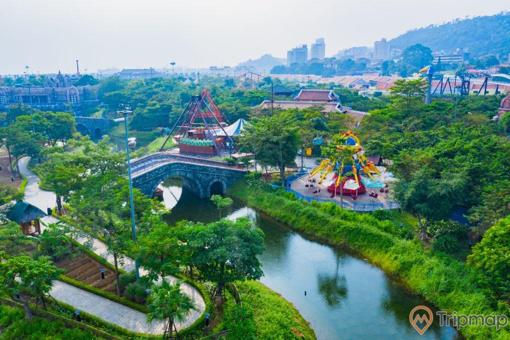 Khu vui chơi giải trí Sun World Ha Long Complex, nhiều cây xanh, hồ nước màu xanh, mô hình thuyền màu nâu, ảnh chụp ban ngày, ảnh chụp từ trên cao
