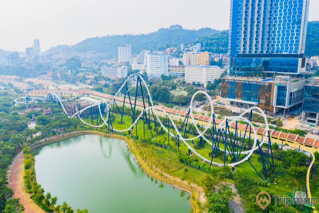 Khu vui chơi giải trí Sun World Ha Long Complex, đường ray màu trắng, Phi long thần tốc, nhiều cây xanh, hồ nước cạnh đường ray, khách sạn mường thanh, nhiều nhà cao tầng phía xa, ngọn núi có nhiều cây xanh phía xa, ảnh chụp ban ngày, ảnh chụp từ trên cao