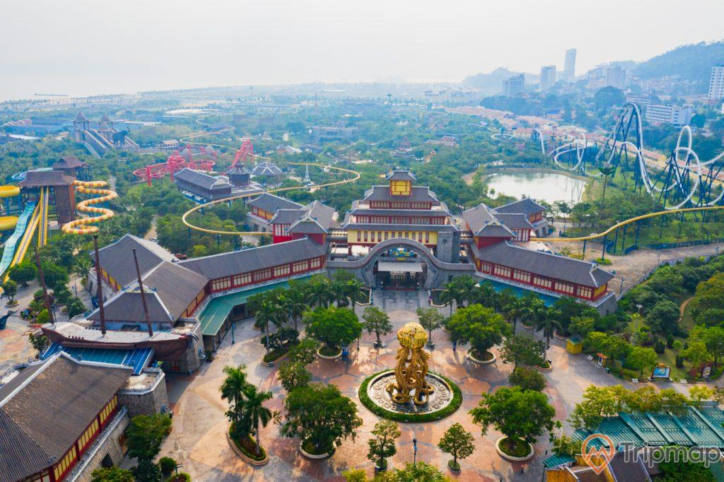 Khu vui chơi giải trí Sun World Ha Long Complex, khuôn viên có nền gạch màu đỏ, nhiều cây xanh, tượng rồng màu vàng, nhà khách có mái ngói màu xám, khu trò chơi ở phía xa, đường ray màu trắng, ảnh chụp từ trên cao, ảnh chụp ban ngày