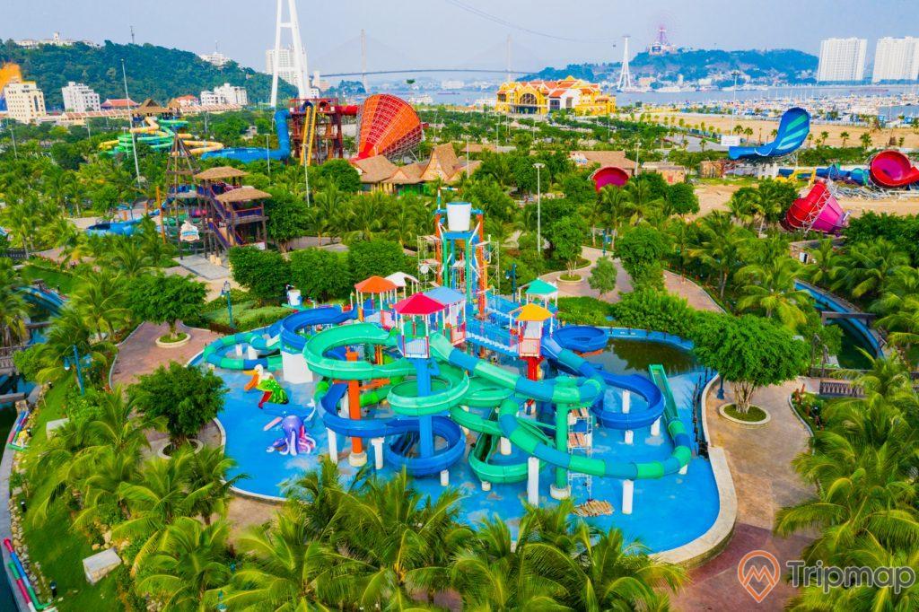 Khu vui chơi giải trí Sun World Ha Long Complex, ống trượt màu xanh trên bể bơi, nhiều cây xanh, nền gạch màu đỏ, cầu bãi cháy ở phía xa, ảnh chụp ban ngày, ảnh chụp từ trên cao