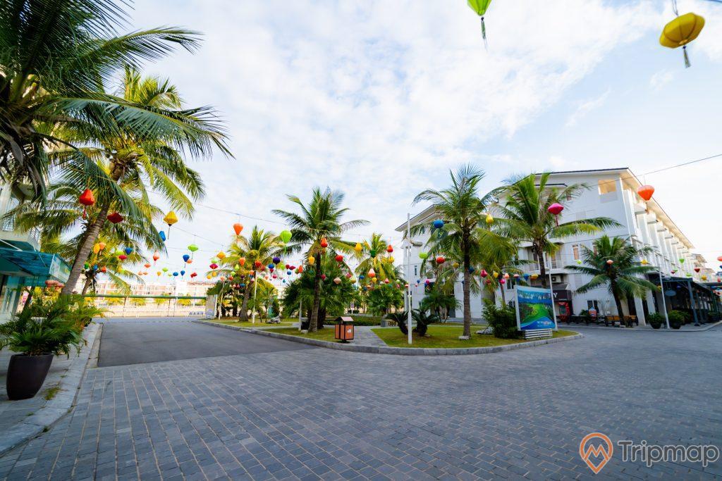 Phố đi bộ Paradise, đường đi bằng gạch màu xám, nhiều cây dừa, nhiều đèn lồng, tòa nhà màu trắng, trời xanh nhiều mây, ảnh chụp ban ngày
