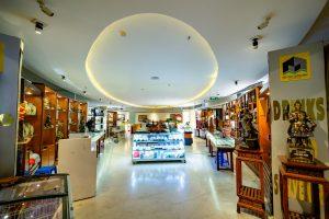Bảo tàng Quảng Ninh, nền gạch bằng đá màu nâu nhạt, trần nhà màu trắng, nhiều tượng bằng đồng, nhiều tủ gỗ