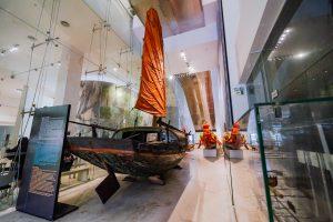 Bảo tàng Quảng Ninh, mô hình thuyền buồm, biển cả và tự nhiên, cánh buồm màu cam, thuyền bằng gỗ, tủ kính, nền nhà màu nâu nhạt, bảng chỉ dẫn màu đen