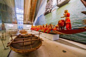 Bảo tàng Quảng Ninh, biển cả và tự nhiên, thuyền màu nâu, bức trangh hòn trống mái, nhiều người đang chèo thuyền màu đỏ, nhiều người mặc áo đỏ, người đàn ông mặc áo đỏ đánh trống, nền nhà màu nâu nhạt