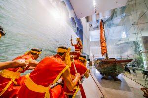 Bảo tàng Quảng Ninh, biển cả và tự nhiên, mô hình người đang chèo thuyền, nhiều người mặc áo đỏ đang chèo thuyền, mô hình thuyền buồm, nền nhà màu nâu nhạt