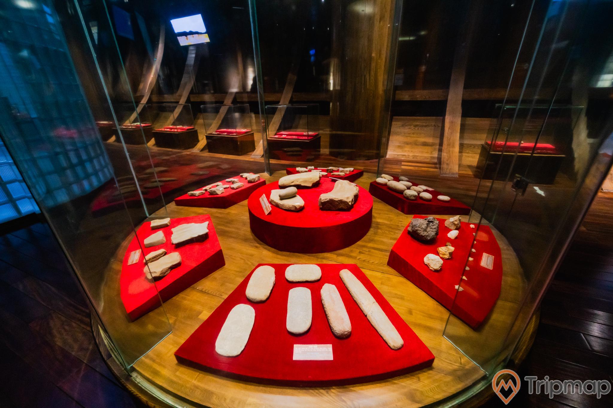 Bảo tàng Quảng Ninh, nơi lưu giữ những giá trị lịch sử, nhiều loại đá được đặt trong tủ kính, tấm gỗ to bên dưới những viên đá