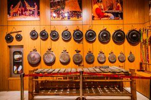 Bảo tàng Quảng Ninh, nơi lưu giữ những giá trị lịch sử, nhiều cồng chiêng màu đen được treo trên bức tường bằng gỗ, nhiều bức tranh được treo trên bức tường bằng gỗ, nền nhà bằng gạch màu trắng