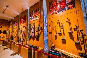 Bảo tàng Quảng Ninh, bộ dây bĩ kéo, bộ gẩy, các loại nhạc cụ được treo trên bức tường bằng gỗ màu nâu, nhiều bức tranh được treo trên tường bằng gỗ màu nâu, nền nhà bằng gạch màu trắng