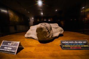 Bảo tàng Quảng Ninh, nơi lưu giữ những giá lịch sử, rùa đá đặt trên bàn bằng gỗ màu nâu, bảng giới thiệu màu đen
