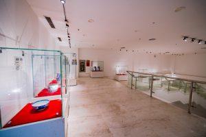 Bảo tàng Quảng Ninh, nơi lưu giữ những giá trị lịch sử, nhiều tủ kính trưng bày hiện vật, nhiều bát đặt trên tấm vải đỏ, nền nhà bằng gạch có hoa văn, trần nhà màu trắng