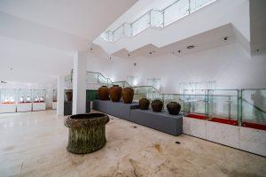 Bảo tàng Quảng Ninh, nơi lưu giữ những giá trị lịch sử, nhiều bình màu nâu được đặt trên bệ màu xám, cột nhà màu trắng, trần nhà màu trắng, nền nhà bằng gạch có hoa văn, nhiều tủ kính