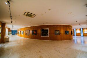 Bảo tàng Quảng Ninh, nơi lưu giữ giá trị lịch sử, hành lang dài, nhiều bức tranh treo trên bức tường bằng gỗ màu nâu, nền nhà bằng gạch có hoa văn, trần nhà màu trắng