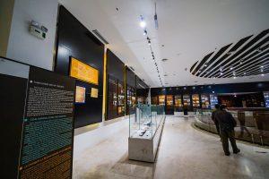 Khu tái hiện lịch sử hình thành mỏ than, bảo tàng Quảng Ninh, nhiều tủ kính trưng bày hiện vật, người đang đi trên nền gạch có hoa văn, bảng giới thiệu màu đen, trần nhà màu trắng