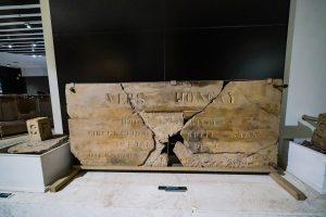 Khu tái hiện lịch sử hình thành mỏ than, bảo tàng Quảng Ninh, hiện vật có chữ bằng gỗ, bức tường màu đen, nền gạch màu trắng